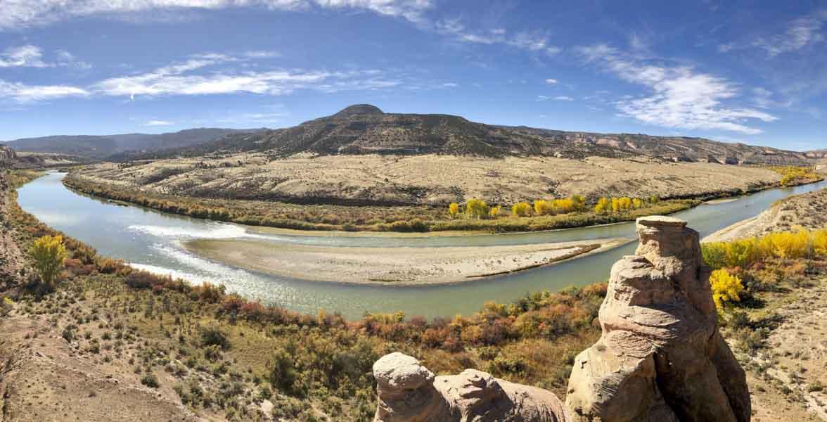 The Colorado River runs through orange cottonwoods.