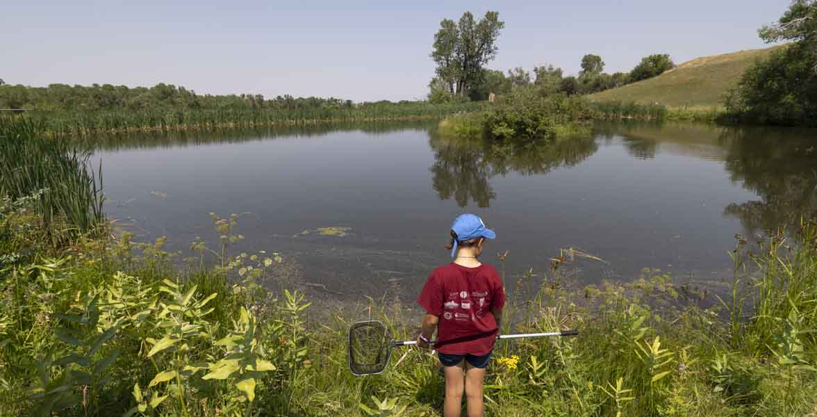 A girl stands in front of a pond with a net.
