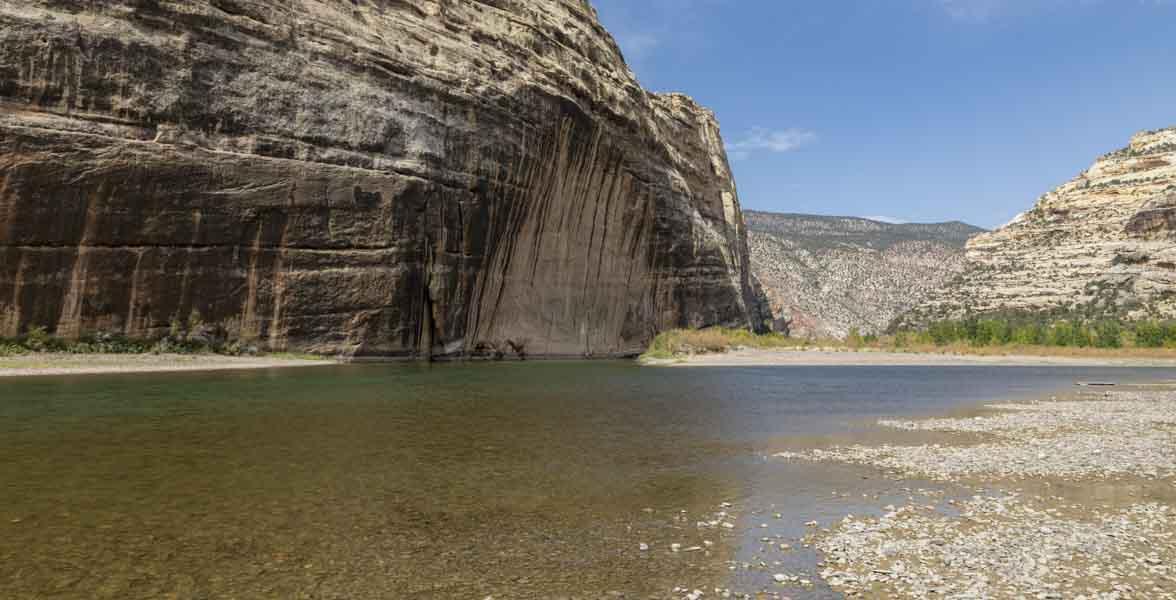 The Green River flows below rocky cliffs.