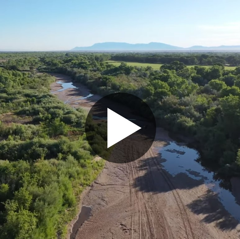 "A landscape view of the Rio Grande River, which itself is mostly dry but is lined with a lush greenbelt of trees and other vegetation. A ""play video"" symbol is superposed on top of the image."